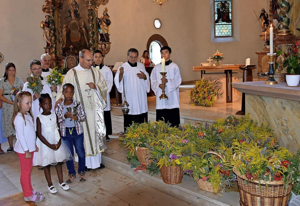 Pfarrer Uwe Schrempp mit Kindern und M...r Kräutersegnung an Maria Himmelfahrt     Foto: Heinz Vollmar