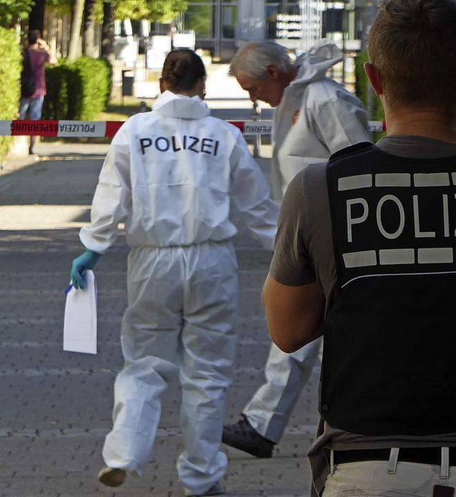 Polizeibeamte sichern Spuren in der Nähe des Tatorts.    Foto: Seller