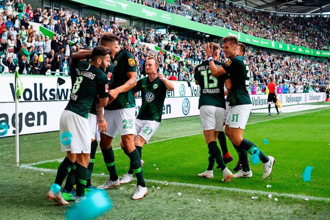Die Wolfsburger bejubeln ihren 2:1-Einstandsieg.  | Foto: dpa