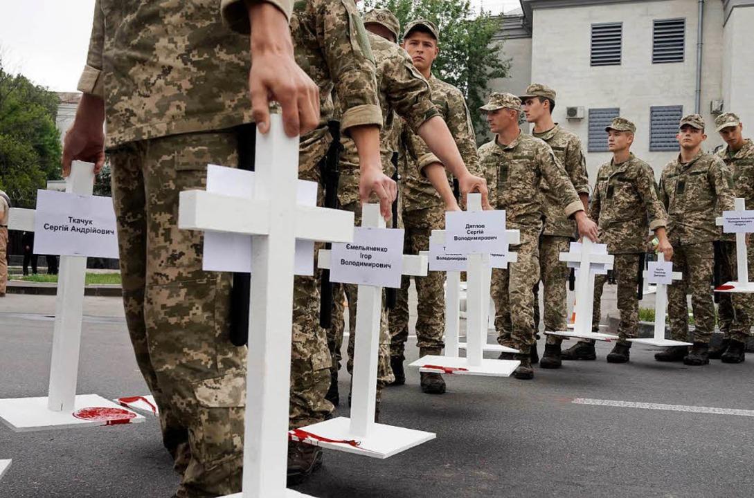 Ukrainische Soldaten tragen Kreuze von...ten in der Ostukraine getötet wurden.   | Foto: DPA