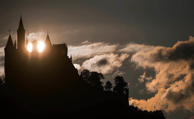Die Sonne geht hinter dem Schloss Hohenzollern auf.  | Foto: dpa
