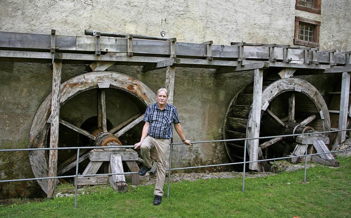 Ortsvorsteher Gerd Müller vor den Wasserrädern der Museumsmühle.  | Foto:  Johannes Renner