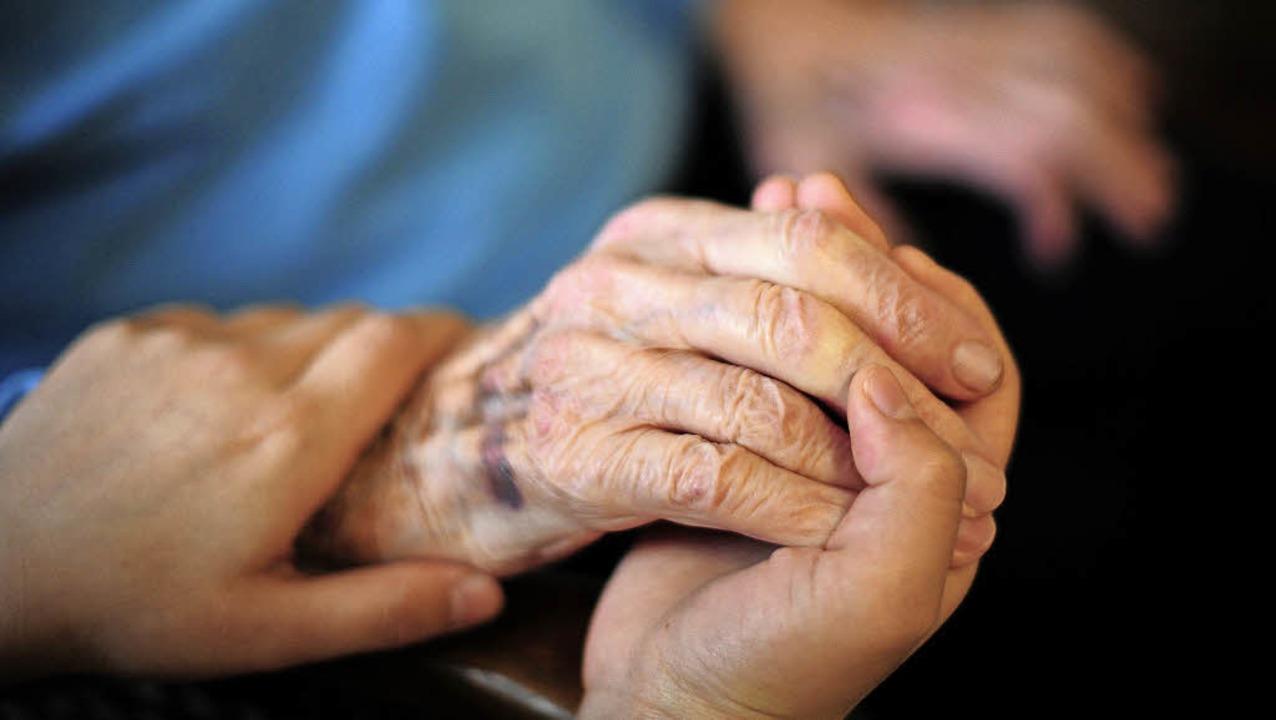 Eine Person hält die Hand einer Patien...patienten sollen davon nichts merken.   | Foto: Symbolfoto: Daniel Reinhardt, DPA