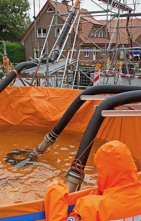 Das Technische Hilfswerk entnimmt Löschwasser aus einem Wasserbecken.   | Foto: dpa