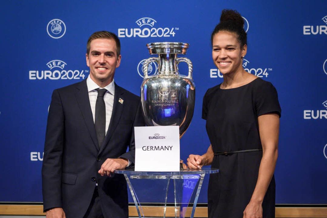 Philipp Lahm und Celia Sasic posieren mit dem EM-Pokal.  | Foto: AFP