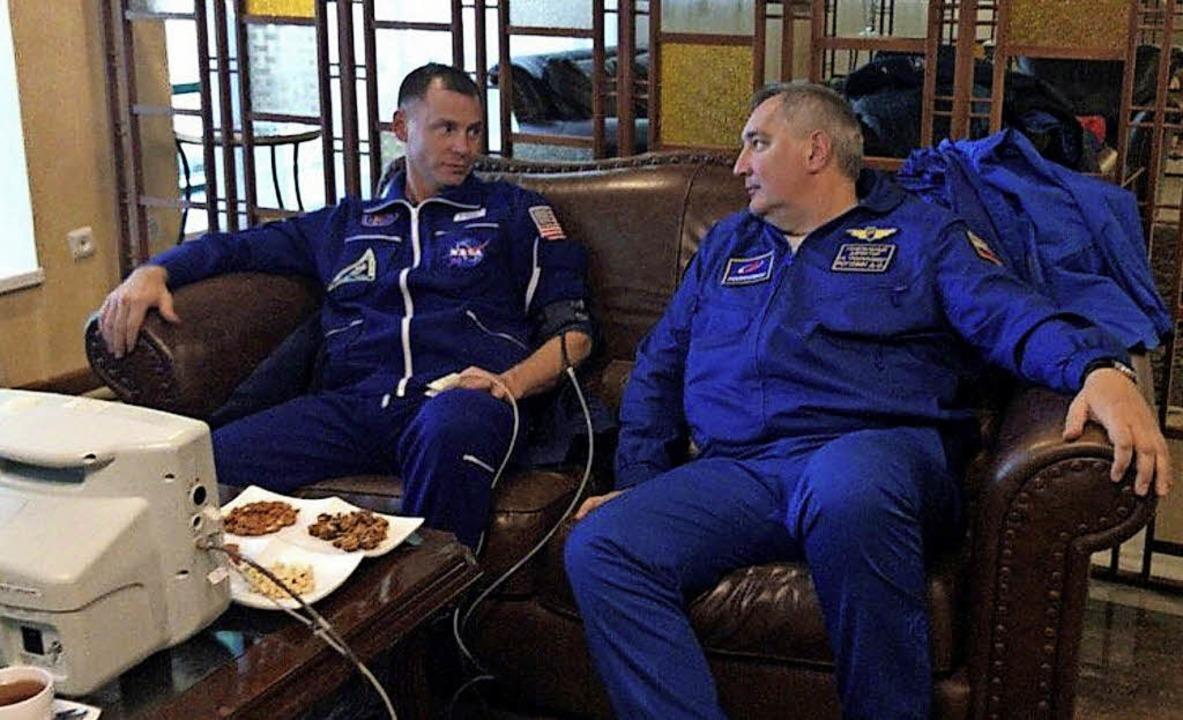 Der US-Astronaut Nick Hague (l) und Dm...ei Hague wird der Blutdruck gemessen.   | Foto: dpa