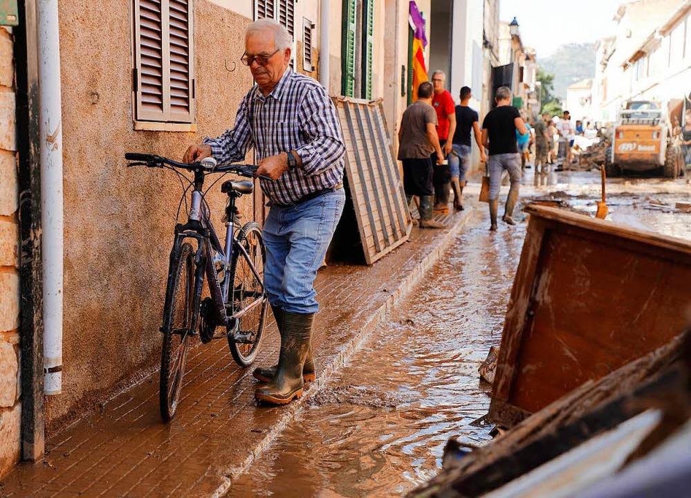 Sant Llorenc Des Cardassar: Ein Anwohn...während Aufräumarbeiten im Gange sind.  | Foto: dpa