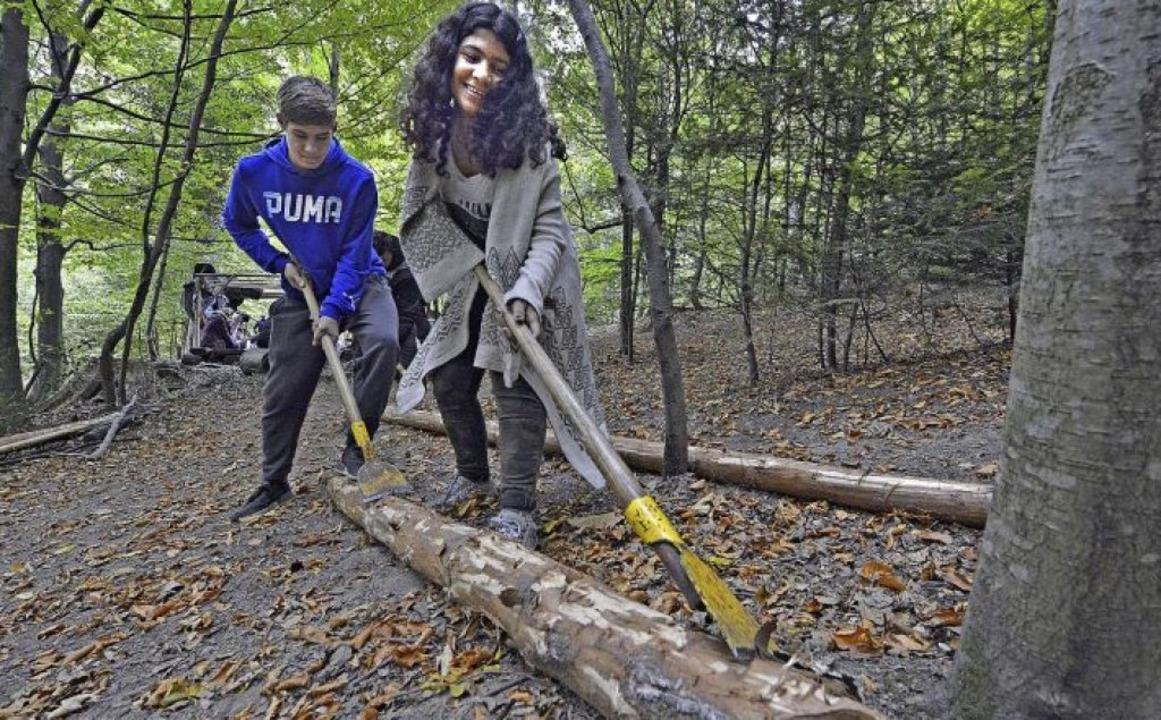 Nach dem Fällen der Bäume sind  Suha (14, vorn) und Alex (13) am Entrinden.    Foto: Michael Bamberger