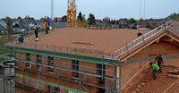 Helfer und Experten decken das Dach