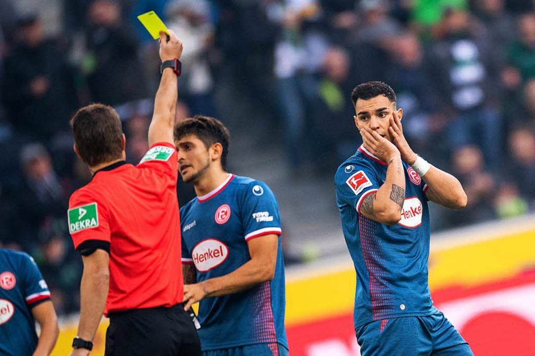 Schiedsrichter Felix Brych (l) zeigt D...gegen Mönchengladbach die Gelbe Karte.  | Foto: dpa