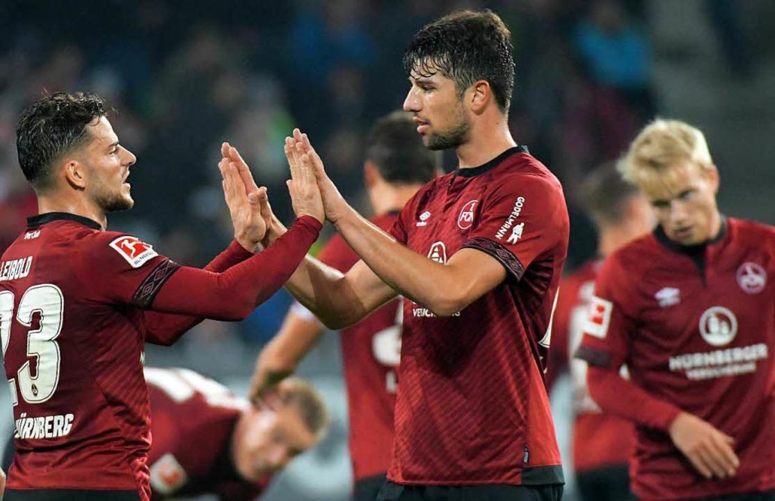 Tim Leibold (l) und Lukas Mühl von Nür...nder nach dem SPiel gegen Augsburg ab.  | Foto: dpa