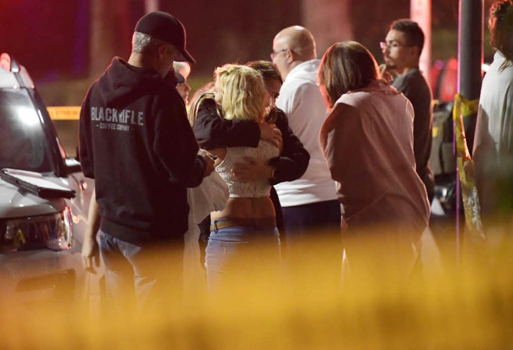 Menschen trösten sich gegenseitig in d...der ein Mann auf Gäste geschossen hat.  | Foto: dpa
