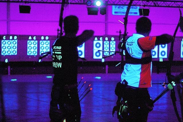 200 Bogenschützen schießen bei UV-Licht auf Neonscheiben