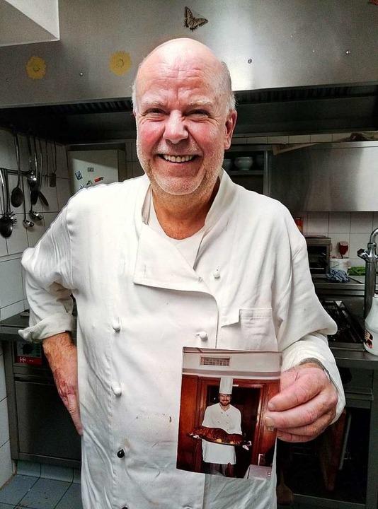 Peter Senn in der Küche mit einem Foto...schon damals servierte er Spanferkel.   | Foto:  gef
