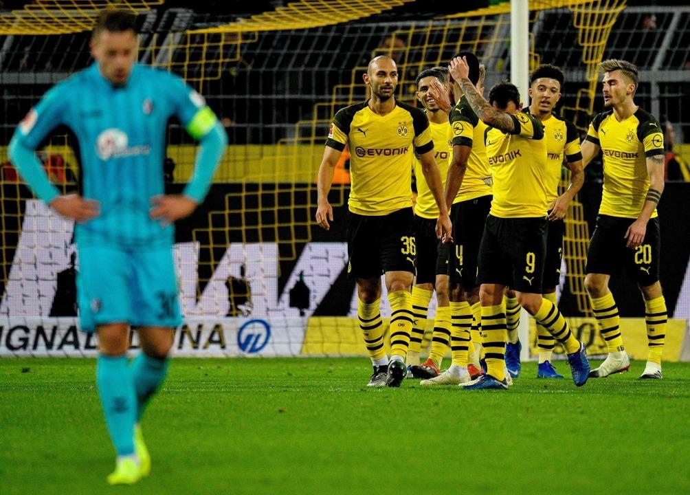 Die Dortmunder feiern, SC-Kapitän Christian Günter scheint geknickt zu sein.  | Foto: AFP