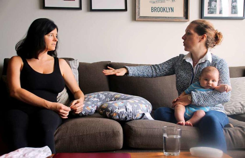 Die junge New Yorker Mutter Lauren (li...r, die den kleinen Elliot im Arm hält.  | Foto: dpa