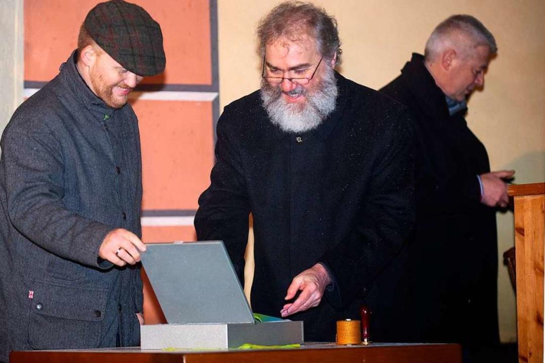 Pfarrer Klemens Armbruster bestückt die Zeitkapsel.    Foto: Wolfgang Scheu