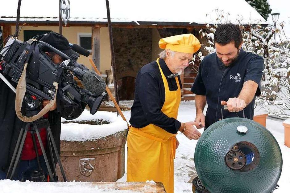 Schnee-Grillen: Steffen Disch zeigt dem französischen Journalisten André Muller (in gelb) die Sellerie auf dem Grill. (Foto: Nikola Vogt)