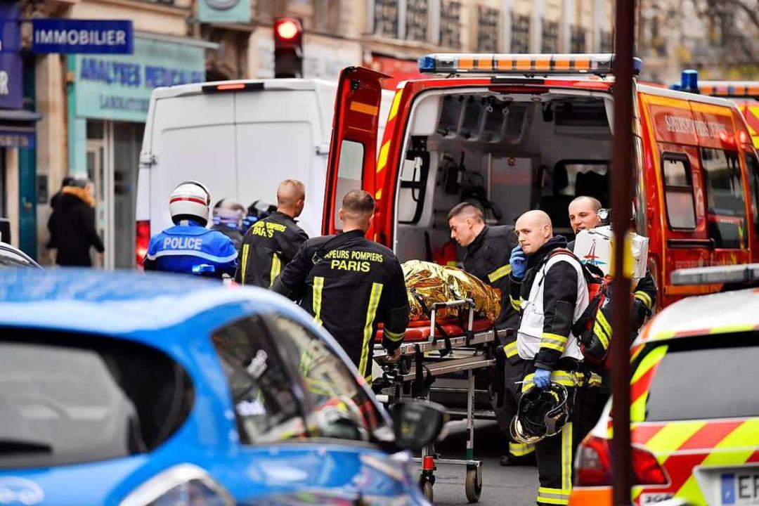 Paris: Feuerwehrleute stehen nach der ...kerei vor einem benachbarten Wohnhaus.  | Foto: dpa