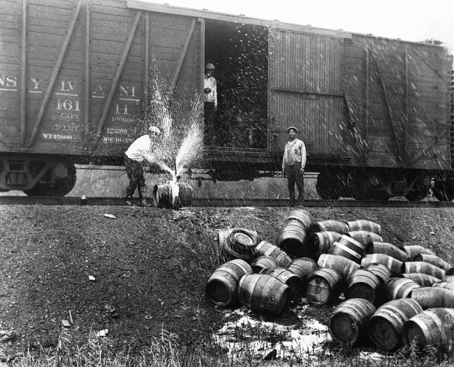 Arbeiter zerstören Bierfässer, die in ...eröl deklariert und beschriftet waren.  | Foto: dpa