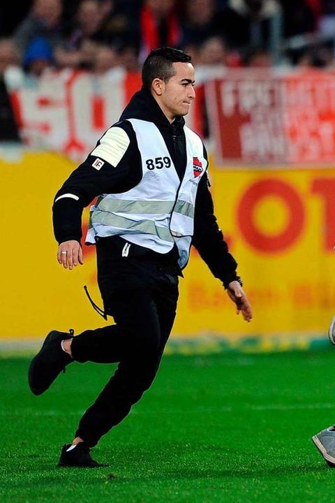 Ein Ordner verfolgt kurz danach einen Flitzer, der übers Spielfeld rennt.  | Foto: Meinrad Schön