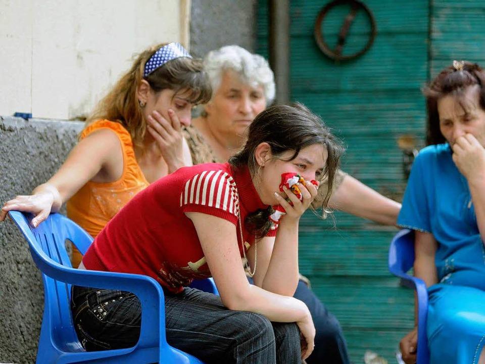 Frauen in Südosstien weinen, weil ihr Dorf zerstört wurde.   | Foto: DPA