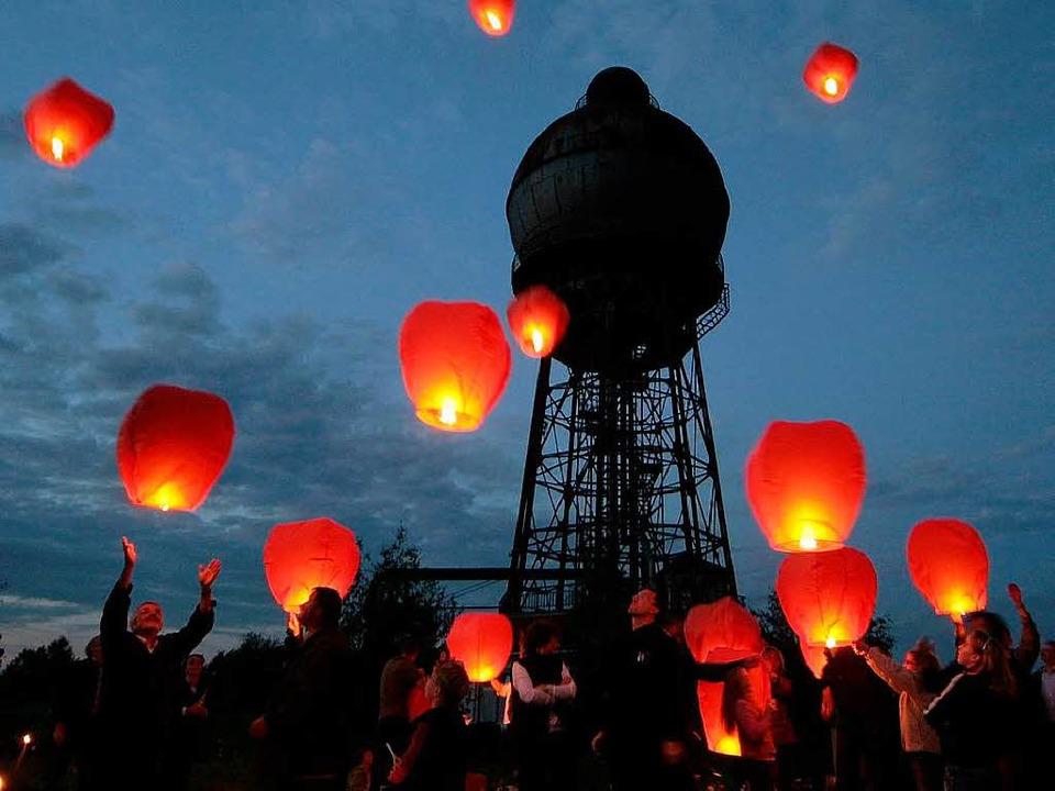 100 Himmelslaternen werden  auf dem hi...  in den abendlichen Himmel gestartet.  | Foto: dpa
