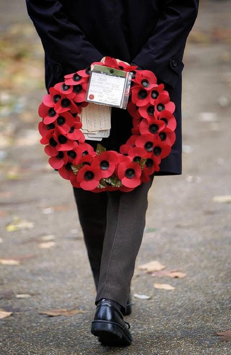 Ein Kranz mit roten Mohnblumen aus Papier erinnert an die Toten.  | Foto: AFP