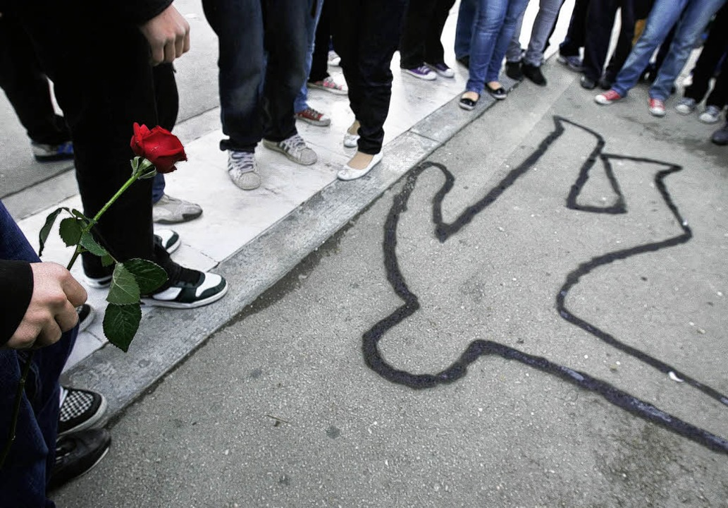 Schüler haben vor dem Parlament in Ath...nen Körper auf die Straße gezeichnet.   | Foto: afp