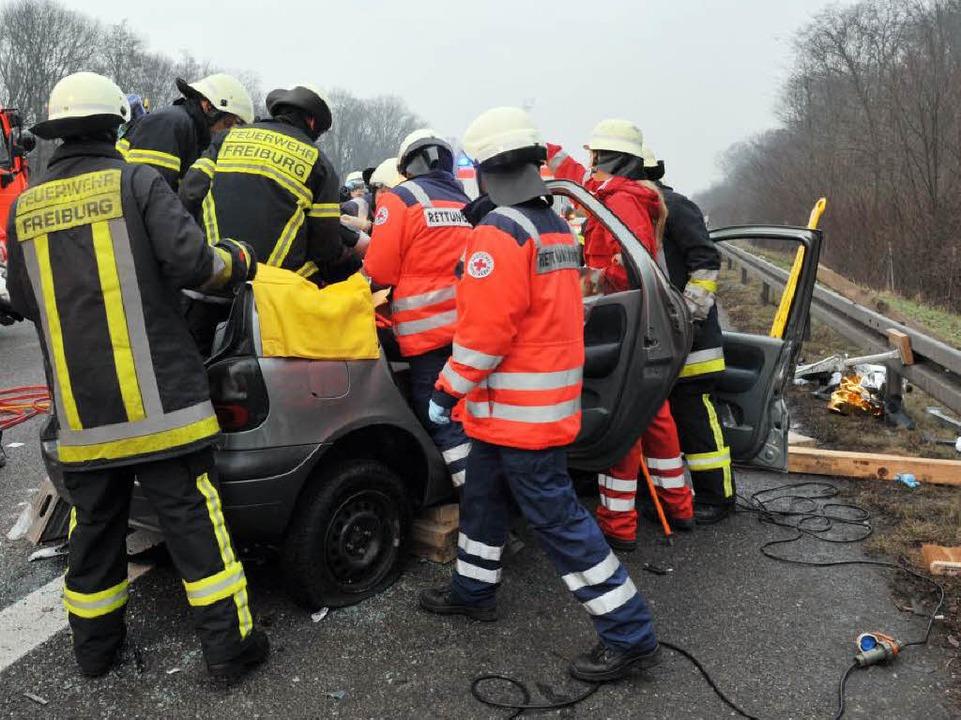 Die Feuerwehr schneidet das Renault-Wrack auf, um die Eingeklemmten zu befreien.  | Foto: Patrick Seeger