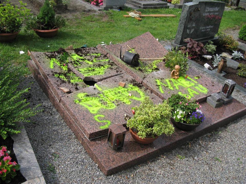 Die zerstörte und beschmierte Grabplatte auf dem Friedhof in Haslach.     Foto: Polizei
