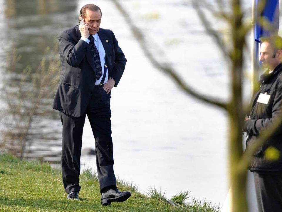 Silvio Berlusconi nutzt den guten Handyempfang am Kehler Rheinufer.  | Foto: ddp