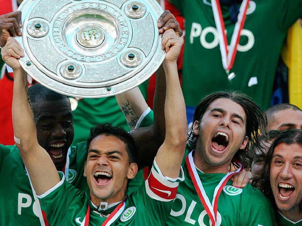 Da ist das Ding: Die Wolfsburger Spieler feiern den Gewinn der Meisterschaft.  | Foto: ddp
