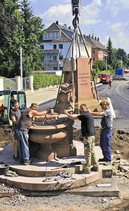 Da schwebt er ein, der kleine Obelisk ... Wintermantel  in Position gebracht.      Foto: Vollmer