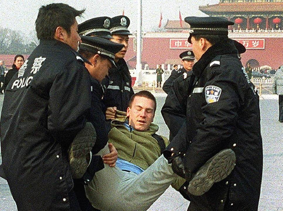 Ein Anhänger der Falun-Gong-Bewegung wird im Jahr  2002 in  Peking verhaftet.   | Foto: DPA