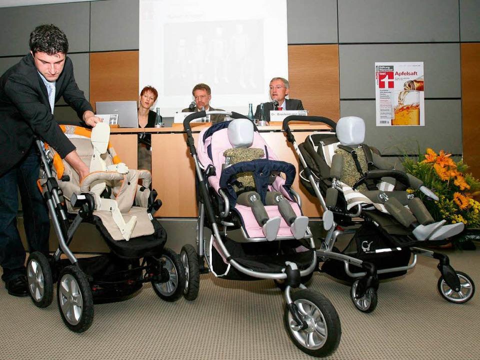 Der Projektleiter der Stiftung Warente...läutert drei der gesteten Kinderwagen.  | Foto: dpa