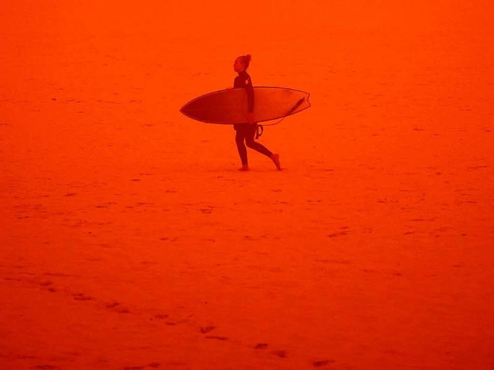 Ganz in Staub gehüllt geht eine mutige Surferin am Bondi Beach Richtung Meer.   | Foto: dpa