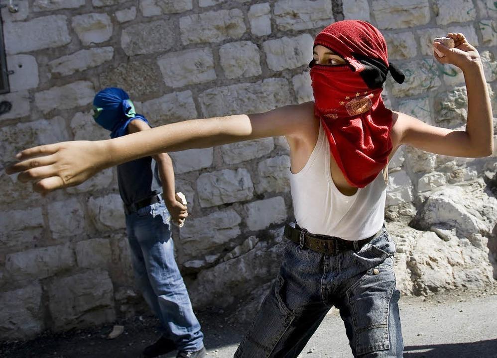 Junge maskierte Palästinenser werfen i...lem Steine auf israelische Polizisten.  | Foto: afp