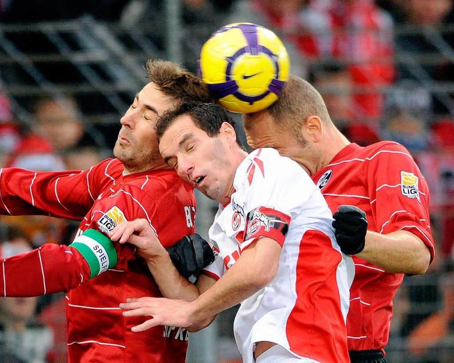 Sandwich: Die SC-Spieler Heiko Butsche...Ivica Banovic (rechts) mit Kölns Petit  | Foto: ddp