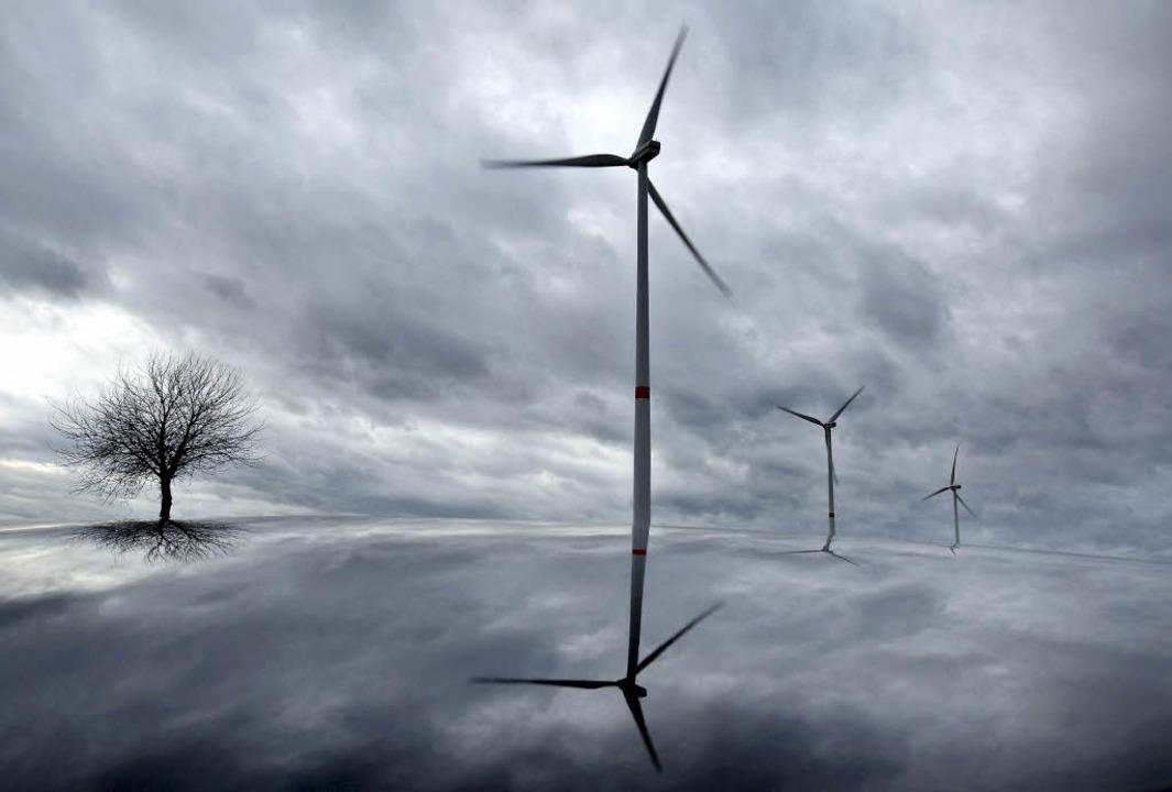 Windräder und ein kahler Baum stehen v...piegelt sich dabei in einem Autodach.   | Foto: dpa