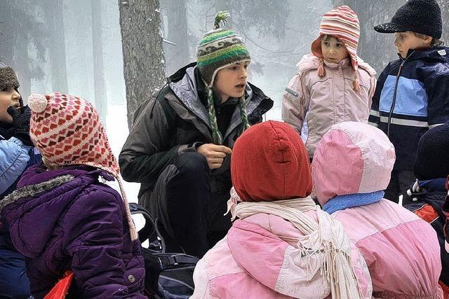 Kinder suchen Tierspuren im Schnee