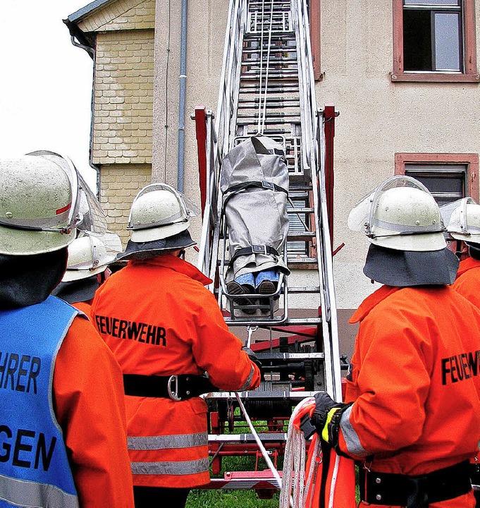 Mit dem  Rettungsschlitten wird eine V...e über die Feuerwehrleiter abgeseilt.     Foto: Monika Rombach