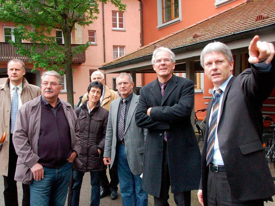Bürgermeister Benitz (rechts) erklärt ...chadensbild in der Staufener Altstadt.  | Foto: Markus Donner