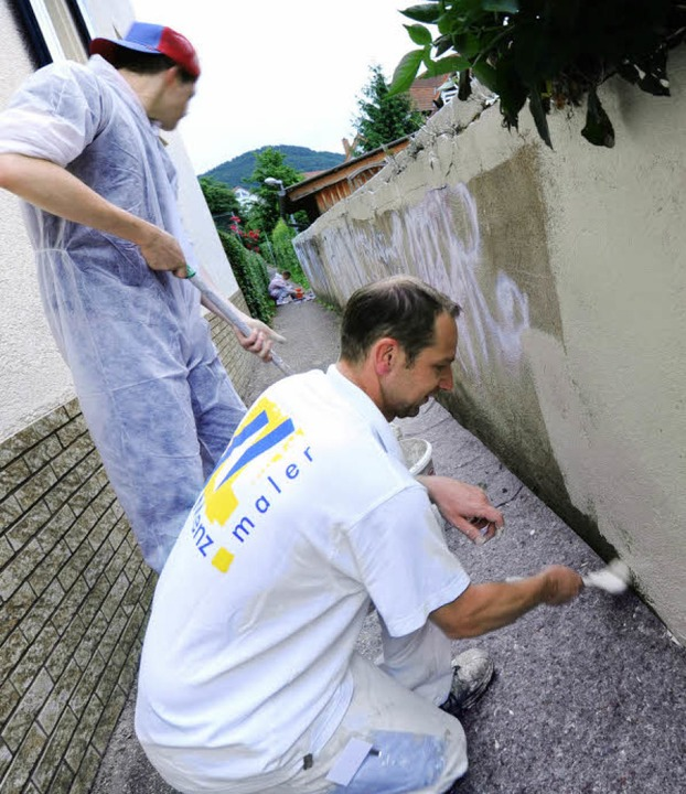 Maler Rüdiger Steigert (vorne) entfern...n,  Graffiti entlang der Ochsengasse.   | Foto: Rita Eggstein