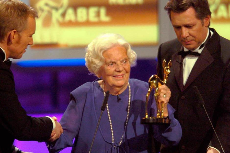2004: Der Moderator Johannes B. Kerner (l) überreicht der Schauspielerin Heidi Kabel bei der 56. Bambi-Verleihung in Hamburg neben ihrem Laudator Jan Fedder (r) das goldene Rehkitz (Foto: dpa)