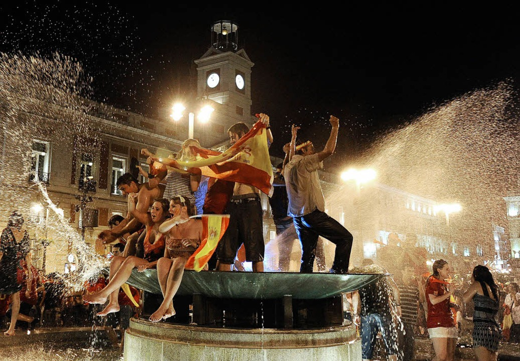 Spanien feiert: Badende Fans an einem ...en an der  Puerta del Sol  in Madrid.   | Foto: afp