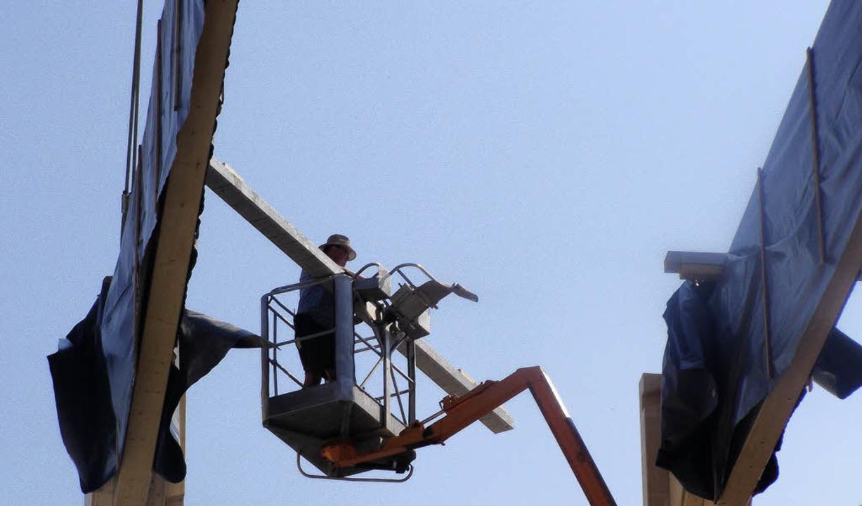 In luftiger Höhe sind die Holzbau-Spezialisten  im Hubsteiger tätig.  | Foto: Liane Schilling
