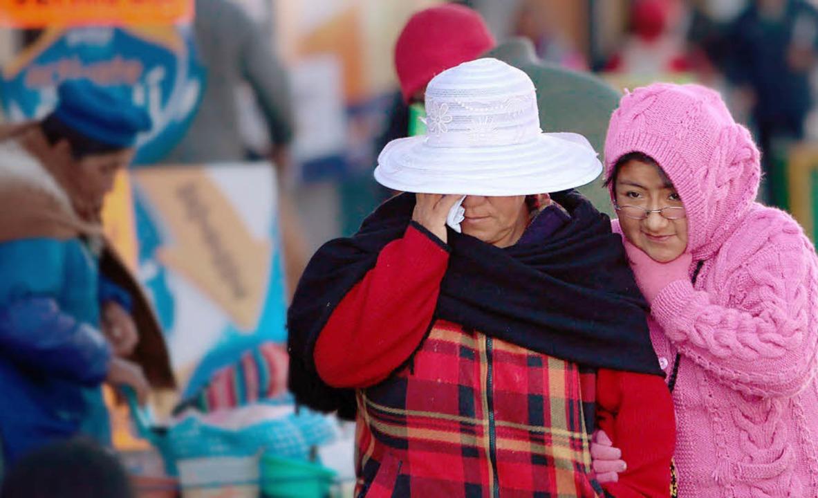 Zwei Frauen in Bolivien schützen sich ...idung vor den frostigen Temperaturen.   | Foto: dpa