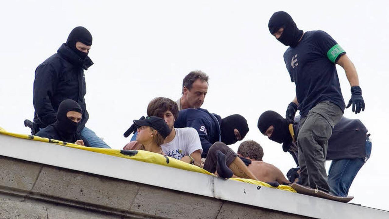 Polizisten mit Tarnkappen holen sieben Demonstranten vom Dach des Nordflügels.    | Foto: dpa
