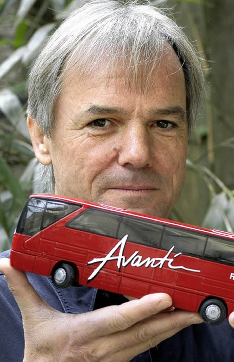 Hans-Peter Christoph mit einer Mini-Ausgabe eines seiner knallroten Reisebusse  | Foto: bz